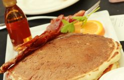 Плита с вкусными блинчиками и беконом на таблице Стоковое Изображение