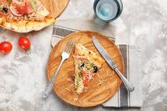 Плита с куском вкусной пиццы на таблице Стоковые Фото