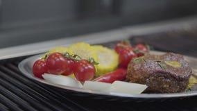 Плита с мясом, мозолью, томатами вишни, лимонным соргом и перцем chili лежа на конце гриля вверх E видеоматериал