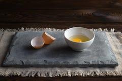 Плита с сырцовым сломленным яйцом, раковиной на бетонной плите стоковые фотографии rf