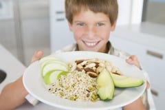 плита удерживания еды мальчика стоковое фото