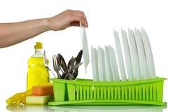 Плиты и столовый прибор на стеллаже для просушки, около детержентных перчаток и губки изолированных на белизне Стоковое Изображение