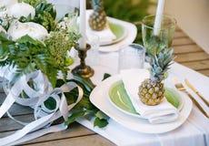 Плиты на таблице украшенной с цветом ананасов, свечей и цветков, зеленых и белых Стоковые Фото