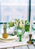 Плиты на таблице украшенной с цветом ананасов, свечей и цветков, зеленых и белых Стоковые Фотографии RF
