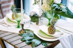 Плиты на таблице украшенной с цветом ананасов, свечей и цветков, зеленых и белых Стоковое Фото