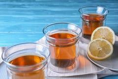 Плиты со стеклами горячих чая и лимона стоковая фотография rf