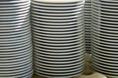 Плиты штабелированные на таблице Комплект белых блюд на таблице на светлой предпосылке Стоковые Изображения RF