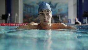 Пловец смотря камеру полагаясь на разделяя пути в бассейне сток-видео