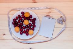 Плодоовощи, блокнот и измеряя лента на деревянной предпосылке Стоковые Изображения