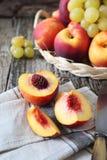 Плодоовощи в плетеной корзине: зеленые виноградины и персики Стоковое Фото