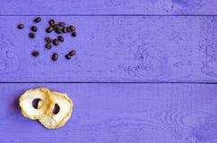 Плодоовощи Яблока candied и пригорошня зерна кофе на фиолетовой деревянной предпосылке Пустой космос стоковая фотография rf
