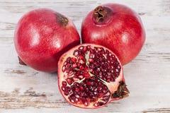 Плодоовощ красного гранатового дерева на деревянной планке, половине с семенами, конце вверх Стоковая Фотография