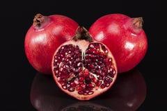 Плодоовощ красного гранатового дерева на черной предпосылке, половинный и весь Стоковые Фотографии RF
