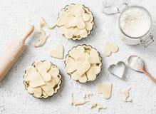Плоская предпосылка выпечки дня ` s валентинки положения Сырцовые tartlets яблока в блюде выпечки и ингридиенты выпечки на светло Стоковая Фотография RF