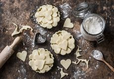 Плоская предпосылка выпечки дня ` s валентинки положения Сырцовые tartlets яблока в блюде выпечки и ингридиенты выпечки на деревя Стоковое Изображение RF