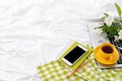 Плоская таблетка положения, телефон, желтая чашка чаю, компьтер-книжка и цветки на белом одеяле с зеленой салфеткой стоковое фото