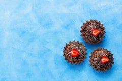 Плоские пирожные положения с сливк и клубниками шоколада на голубой предпосылке скопируйте космос стоковая фотография
