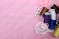 Плоские положение или взгляд сверху, игла, scissor, продевают нитку, метр портноя, на розовой предпосылке стоковая фотография rf