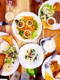 Плоские положение и взгляд сверху салата, зажаренного стейка говядины, половины хлеба масла, шпината с сыром, супа гриба и много  Стоковое Изображение RF