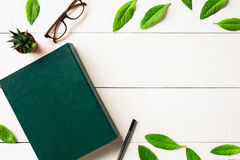 Плоские стекла и ручка книги положения на белой деревянной предпосылке Стоковые Фотографии RF