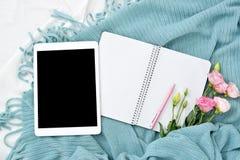 Плоские таблетка, телефон, чашка кофе и цветки положения на белом одеяле с шотландкой бирюзы стоковые фото