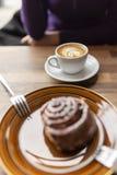 Плоский белый кофе с плюшкой циннамона вне--фокуса на переднем плане стоковые изображения