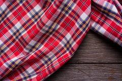 Плоский взгляд положения тартана текстурировал шарф на деревянной предпосылке Стоковая Фотография RF
