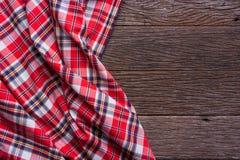 Плоский взгляд положения тартана текстурировал шарф на деревянной предпосылке Стоковая Фотография