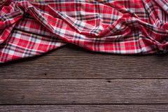 Плоский взгляд положения тартана текстурировал шарф на деревянной предпосылке Стоковое фото RF