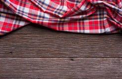 Плоский взгляд положения тартана текстурировал шарф на деревянной предпосылке Стоковые Изображения