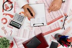 Плоский взгляд сверху бизнесмена работая и высчитывая финансы, читает и пишет отчеты r стоковая фотография