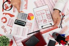 Плоский взгляд сверху бизнесмена работая и высчитывая финансы, читает и пишет отчеты r стоковые фото