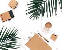 Плоский модель-макет места для работы домашнего офиса положения с доской сзажимом для бумаги, тропическими листьями стоковое изображение