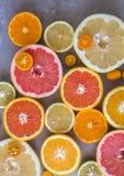 Плоский положенный взгляд сверху красивого разнообразия свежей неполной вырубки цитрусовых фруктов Апельсины, лимоны, Клементин,  стоковые изображения