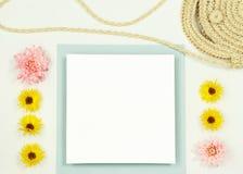Плоский положенный модель-макет рамки с цветками лета и сумкой соломы стоковые фото