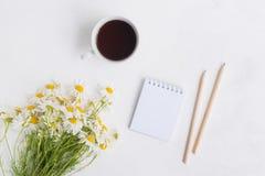Плоский положенный стол с белыми маргаритками, тетрадью и чашкой с чаем стоковая фотография rf