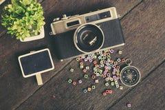 Плоский состав положения винтажной камеры, компаса, зеленого растения и блока слова на деревянном столе Стоковая Фотография
