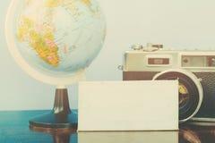 Плоский состав положения винтажной рамки камеры, глобуса и холста на идеале деревянного стола для каникул и концепции перемещения Стоковое фото RF