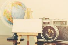плоский состав положения винтажной рамки камеры, глобуса, мольберта и холста на деревянном столе Стоковая Фотография RF