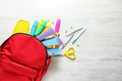 Плоский состав положения с рюкзаком, космосом канцелярских принадлежностей школы для текста на светлой предпосылке стоковое фото rf