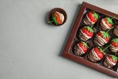 Плоский состав положения с шоколадом покрыл клубники на серой предпосылке Стоковое фото RF