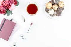 Плоский стол домашнего офиса положения Женственное место для работы с дневником, цветками, помадками, аксессуарами моды Концепция Стоковая Фотография