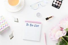 Плоский стол домашнего офиса положения Женственное место для работы с для того чтобы сделать список, пион цветет, косметики, ювел стоковые фотографии rf