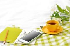 Плоский телефон положения, желтая чашка чаю и цветки на белом одеяле с зеленой салфеткой стоковые изображения rf