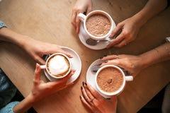 Плоское изображение положения сверху: 3 руки держа 3 чашки coff Стоковое Изображение