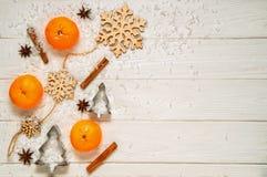 Плоское положение Белая деревенская таблица с tangerines, циннамон, анисовк-звезда, прессформы рождества для печенья в форме рожд стоковая фотография