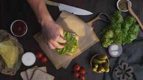 Плоское положение делать сэндвич с отрезанными беконом и салатом, шеф-поваром добавляет салат к сэндвичу на деревянной доске, дел сток-видео