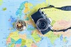 Плоское положение камеры Mirrorless и опарника стекла заполненных при бронзовые монетки изолированные на предпосылке карты мира Стоковое фото RF