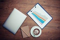 Плоское положение компьтер-книжки при диаграмма и горячий кофе устанавливая на деревянной таблице Стоковая Фотография RF