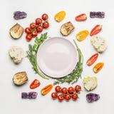 Плоское положение красочных ингридиентов овощей салата вокруг пустой плиты с приправой на белой предпосылке, взгляд сверху Стоковые Фотографии RF
